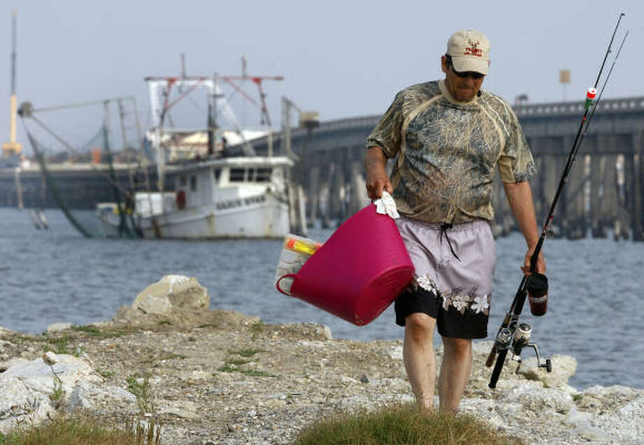 Leroy Sebring of Van Buren, Ark., walks with his fishing gear while vacationing in Grand Isle, La., Wednesday, April 20, 2011. Grand Isle is a coastal community centered around fishing and tourism that was heavily impacted by last year's Deepwater Horizon oil spill. One year after the nation's worst offshore oil spill began, solemn ceremonies will mark the disaster Wednesday and underscore the delicate healing that is only now taking shape. Photo: Patrick Semansky, AP
