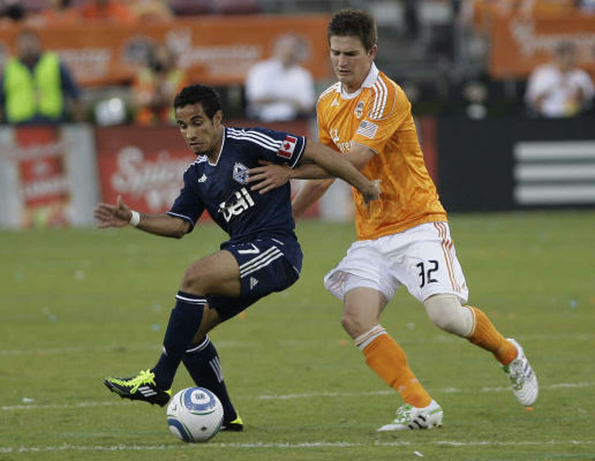 Bobby Boswell, right, of the Houston Dynamo shoves Camilo of the Vancouver Whitecaps.