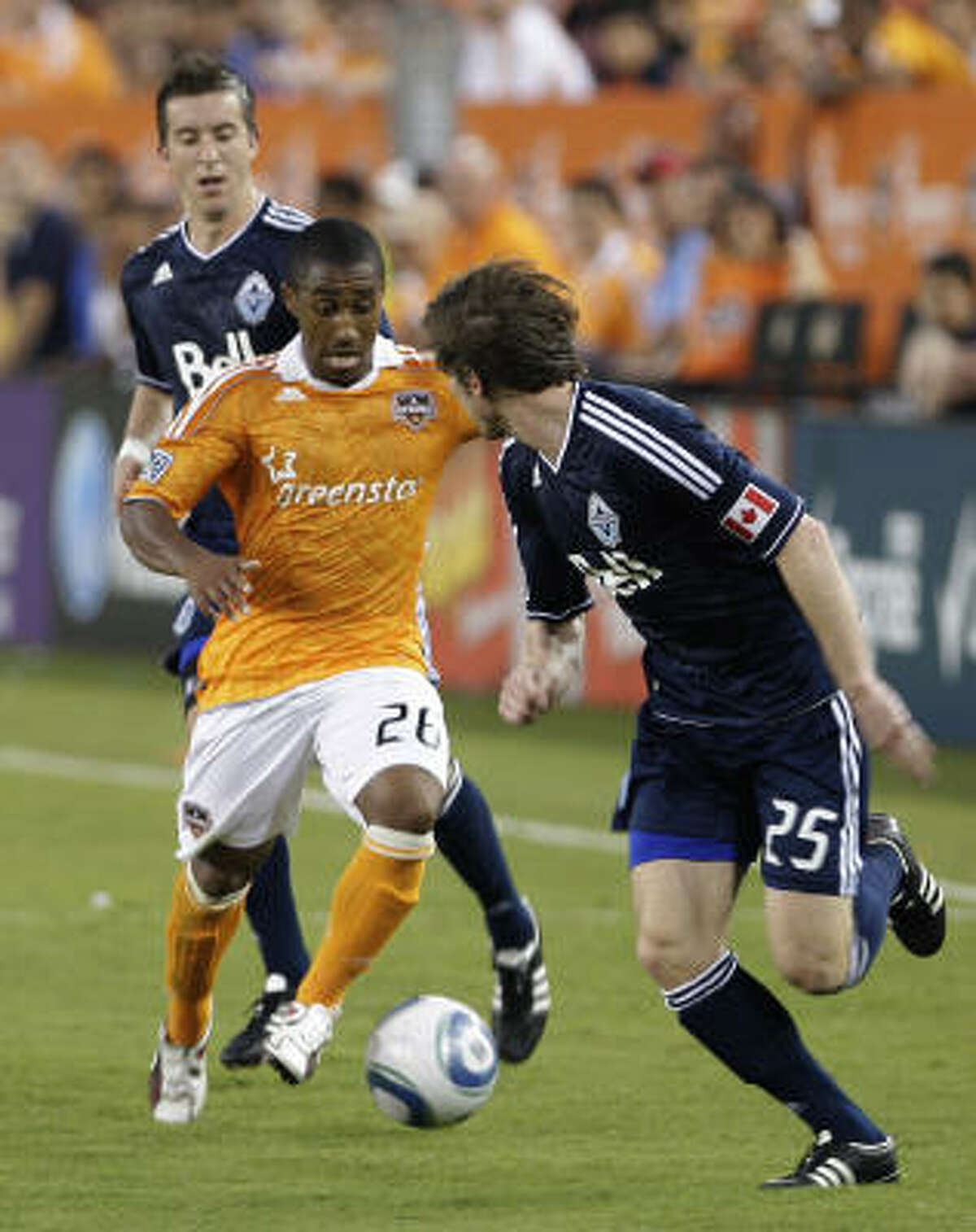 Dynamo's Corey Ashe dribbles the ball around Jonathan Leathers (25) of the Vancouver Whitecaps.