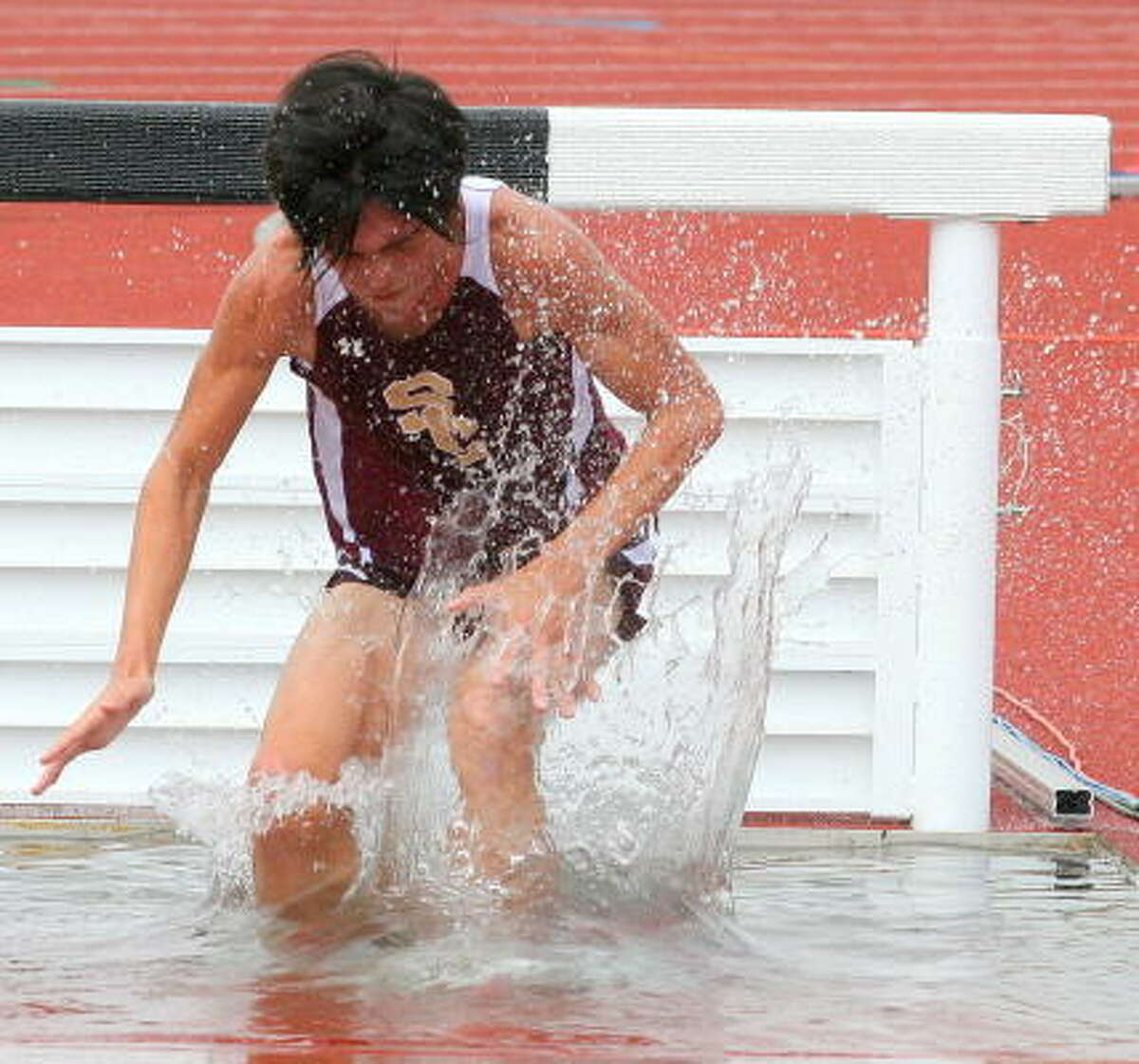 Summer Creek's Ben Sprouse makes a big spash in the the 2000-meter steeplechase.