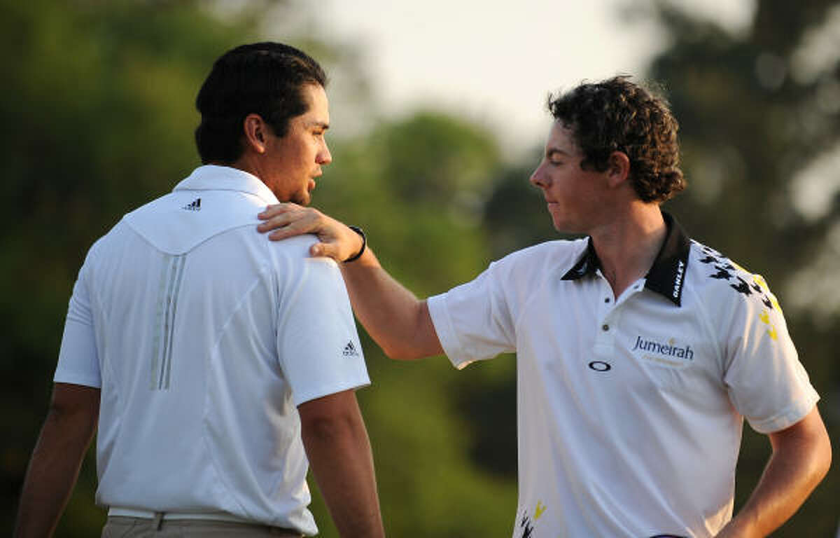Rory McIlroy of Northern Ireland (R) pats Jason Day of Australia on the back after finishing on the 18th hole green on day three of the 2011 Masters Tournament.