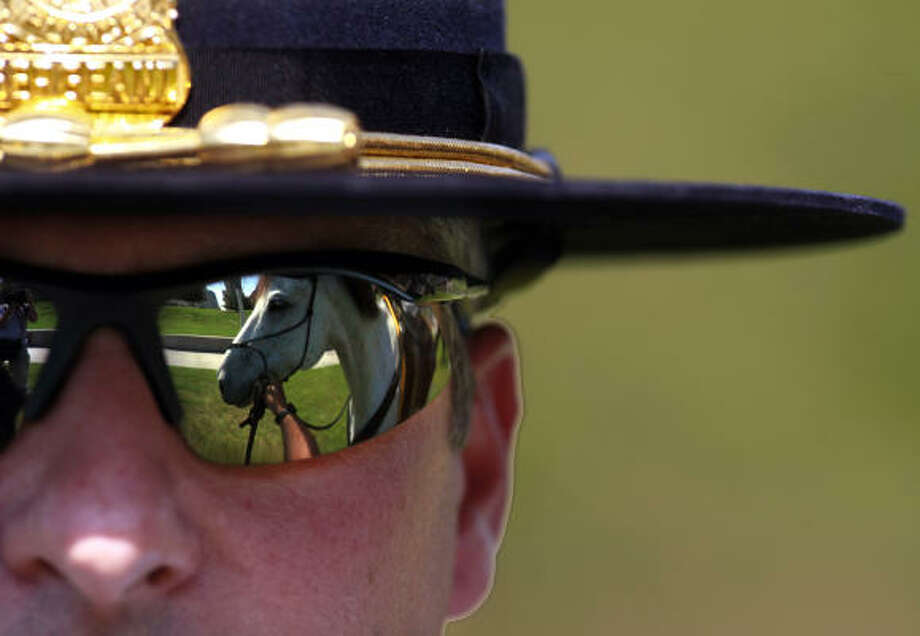 During his first day on the job, Sgt. David Cadieux has his horse, Hanner, reflected in his sunglasses as they take a break in Sesquicentennial Park in downtown Houston. The mounted patrol is in jeopardy of suffering from cuts or being dropped from the force all together due to budget cuts at the department. Photo: Johnny Hanson, Houston Chronicle