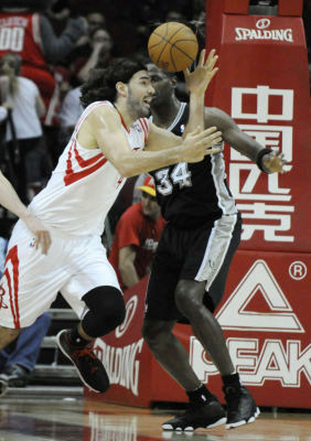 Rockets forward Luis Scola, left, tries to maintain control of the ball while under pressure from San Antonio's Antonio McDyess during the first half.