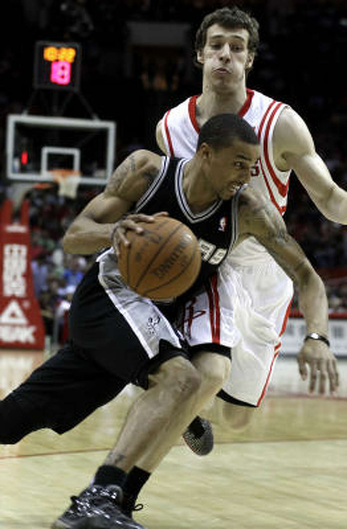 San Antonio's George Hill, front, tries to drive the ball past Rockets guard Goran Dragic.