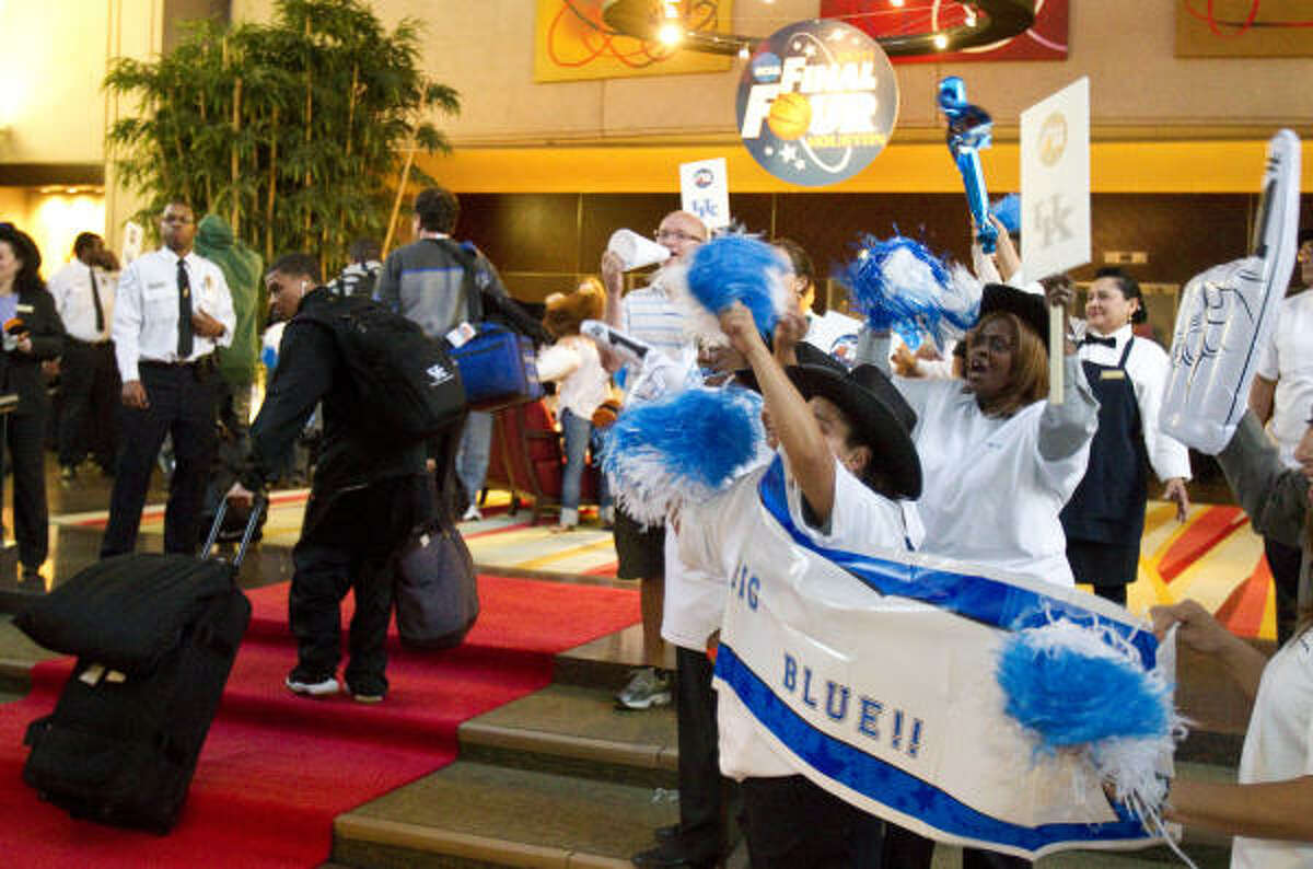 Hilton Post Oak employees and a few fans cheer as the Kentucky men's basketball team walks through the lobby of the Hilton Post Oak.