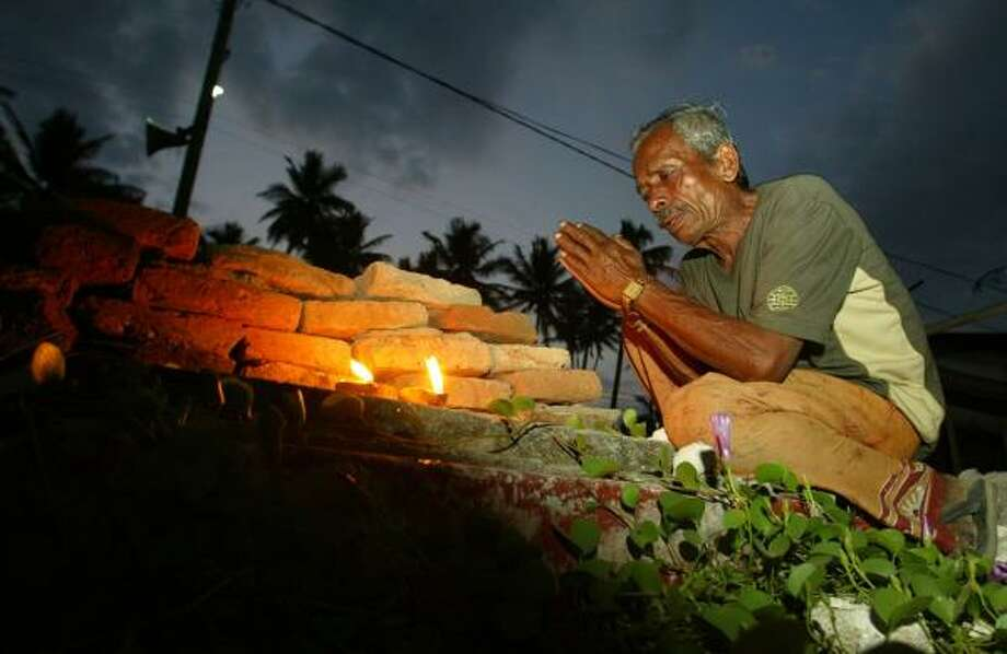 Sattayapala prays at the site where his wife died in the 2004 tsunami at Peraliya, south of Colombo, Sri Lanka. After 40,000 people died, there was still no full-scale change in the island's society as corrupt officials dipped into the overflowing humanitarian cash box. Photo: Gemunu Amarasinghe, ASSOCIATED PRESS
