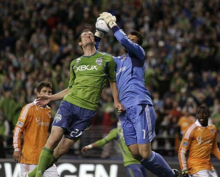 March 25: Dynamo 1, Sounders 1 Seattle's Nate Jaqua, center left, tries for a header against Dynamo goalkeeper Tally Hall during Friday night's game at Qwest Field in Seattle. Photo: John Lok, AP