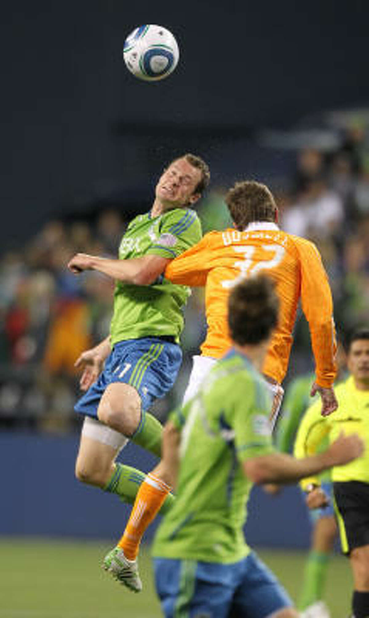 Seattle's Nate Jaqua, left, heads the ball against Dynamo defender Bobby Boswell.