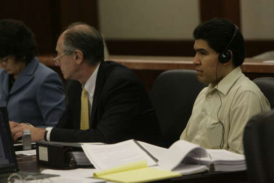 Juan Quintero, right, listens on headphones to a translator during his capital murder trial. He faces a possible death sentence for the 2006 slaying of Houston police Officer Rodney Johnson. Photo: Julio Cortez, Houston Chronicle