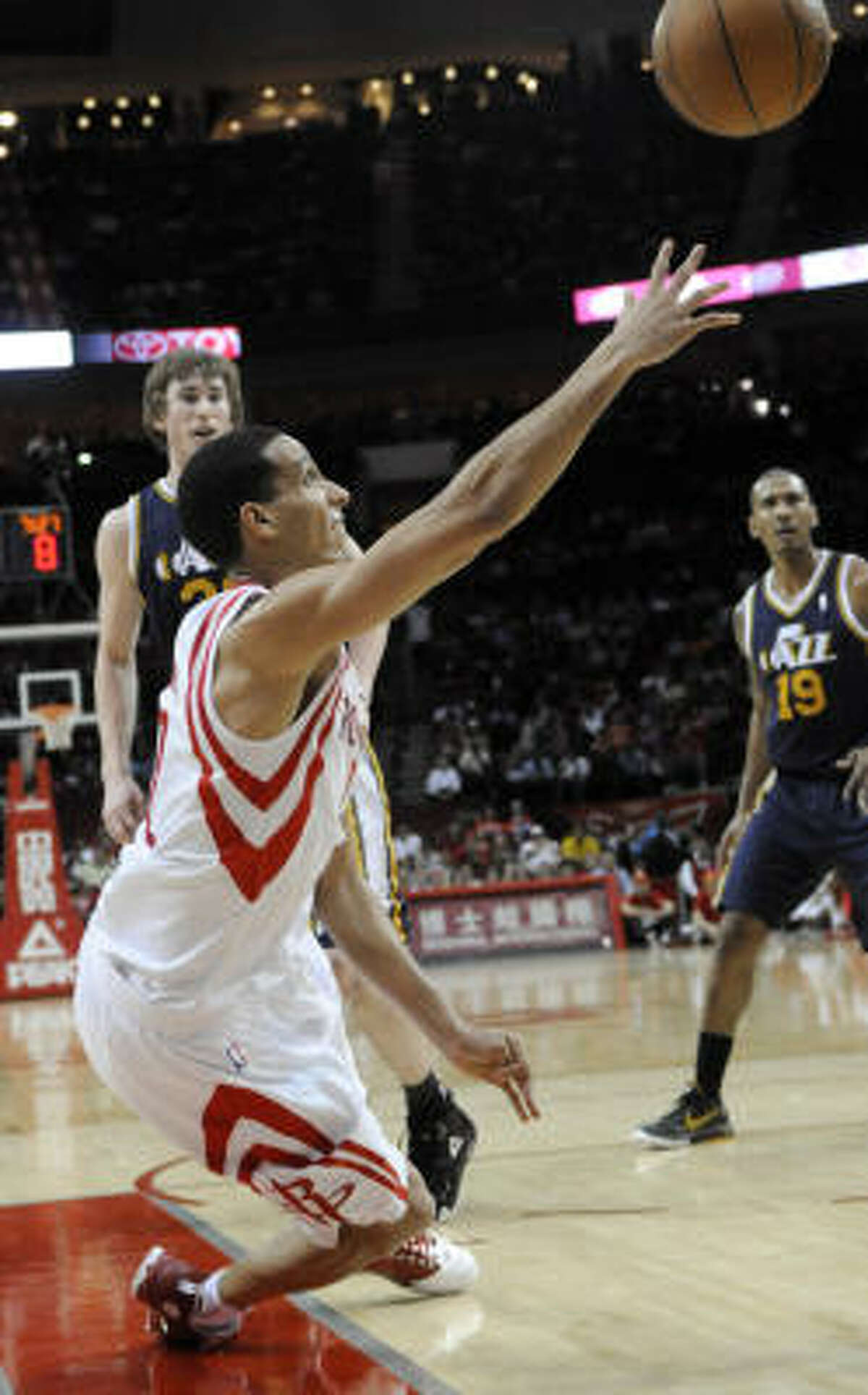 Rockets shooting guard Kevin Martin, foreground, loses his balance after being fouled by Jazz forward Gordon Hayward, back, as Utah's Raja Bell (19) looks on.