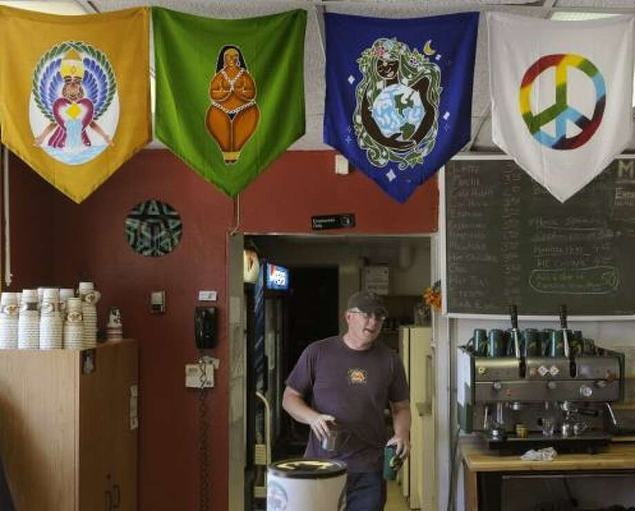 Jesse Walter, owner of a Denver coffee shop/community center that caters to pagans, prepares coffee for a customer. Photo: KARL GEHRING, DENVER POST