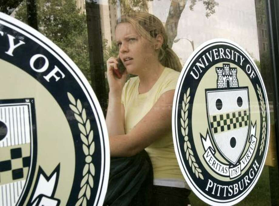 Sara Loughran, a graduate student at the University of Pittsburgh, talks on her cell phone Wednesday. The head of the university's Cancer Institute advised faculty and staff to limit cell use. Photo: KEITH SRAKOCIC, ASSOCIATED PRESS