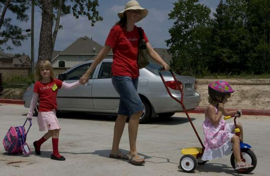 Katie Molho, 5, left, heads home with her mother, Cathy, and sister, Daira, 3, after her first day in kindergarten in Humble. Photo: JAMES NIELSEN, CHRONICLE
