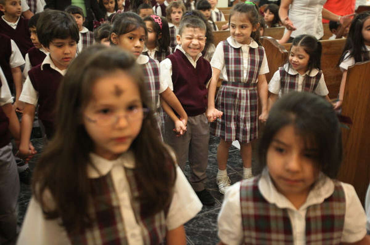 Adam Rodriguez prays the Our Father with kindergarden classmates and students of the Our Lady of Guadalupe Catholic School during mass on Ash Wednesday.