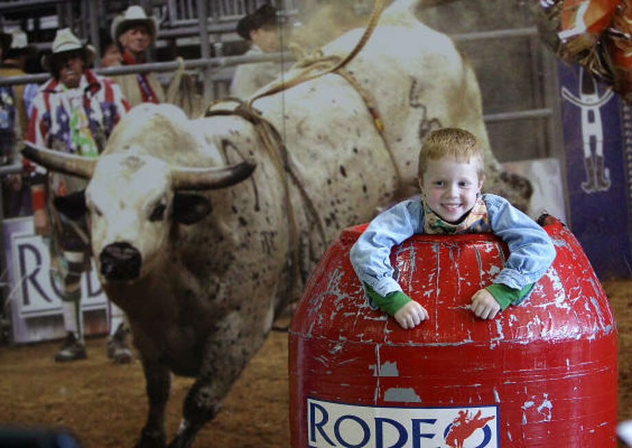 Kevin Blake, 5, of Pearland, gets his photo taken in a bullfighter's barrel at the Houston Livestock Show and Rodeo. Photo: Karen Warren, Houston Chronicle