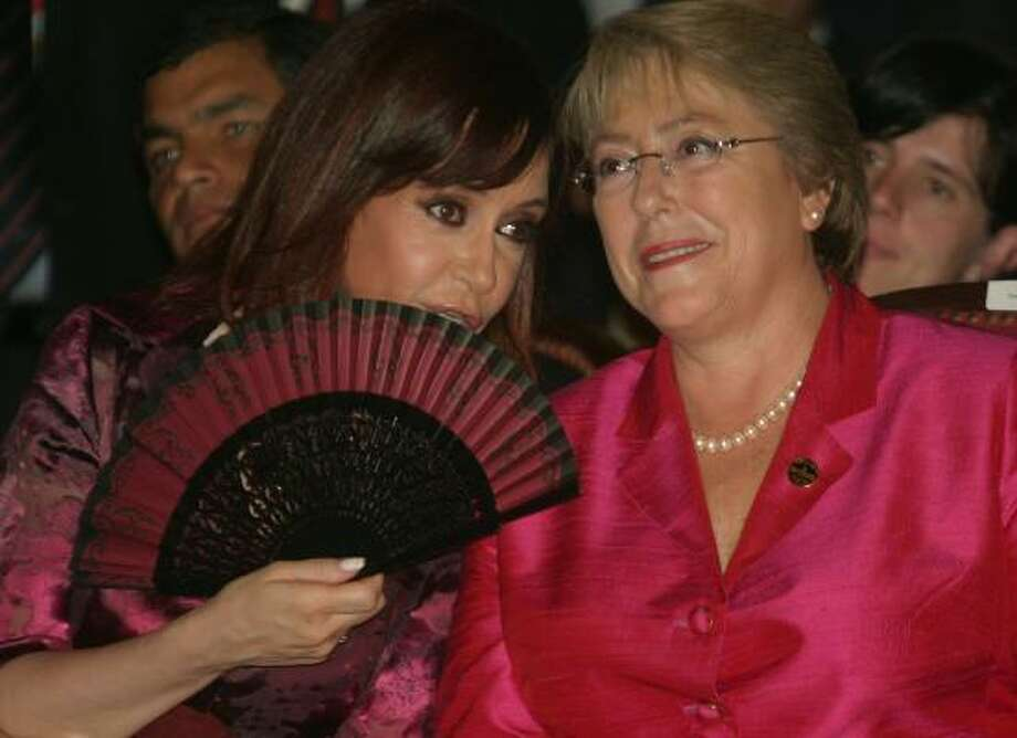 Argentine President Christina Fernandez de Kirchner, left, speaks to Chilean President Michelle Bachelet during the inauguration of Paraguay's president, Fernando Lugo, earlier this month. Bachelet is campaigning for legislation to equalize wages between men and women in Chile. Photo: JORGE ROMERO, AFP/GETTY IMAGES