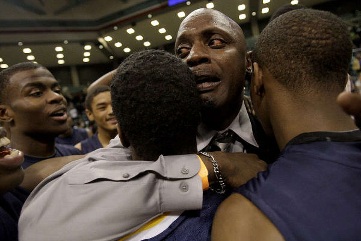 La Marque head coach Cedric Mason hugs some of his players after Saturday's win over Ball.