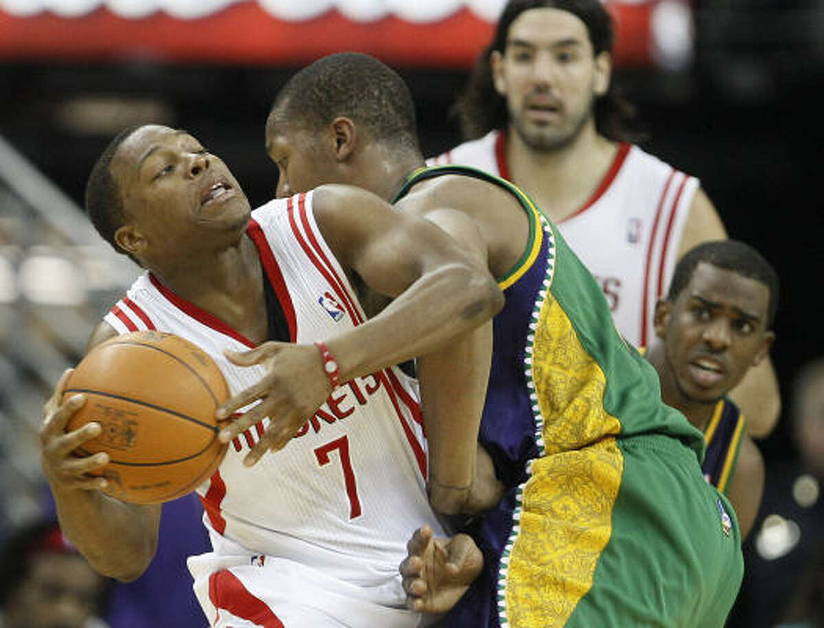 Rockets point guard Kyle Lowry (7) attempts to drive past Hornets forward David West as Rockets forward Luis Scola, top rear, and Hornets point guard Chris Paul watch the play.