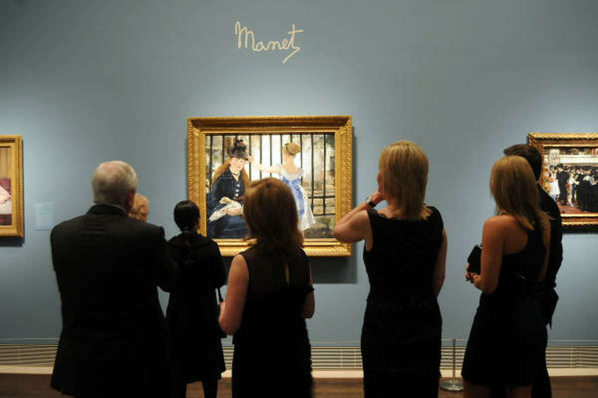Patrons browse the exhibit before a dinner celebrating the exhibition Impressionist and Post-Impressionist Masterpieces from the National Gallery of Art at the Museum of Fine Arts Houston.