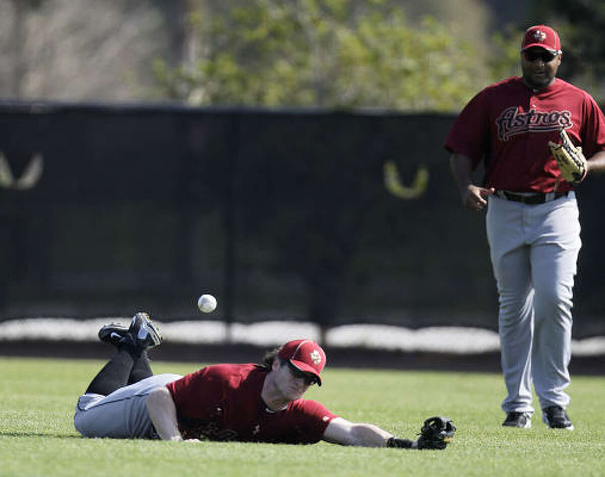Astros outfielder Jon Gaston dives in vain for a fly ball as Carlos Lee watches during drills Monday.