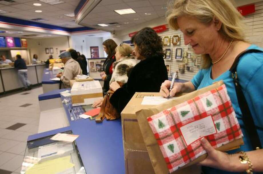 Margaret Miller makes some last-minute preparations before mailing Christmas presents at the University Station post office on Monday. Photo: MAYRA BELTRÁN, CHRONICLE