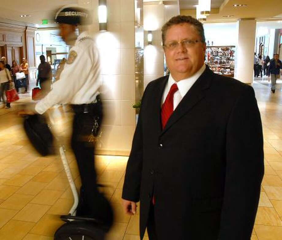 "Edward Guinn speeds past Galleria general manager David Anderson. ""We've got officers on Segways, which puts them about a foot off of the ground and, obviously, makes them more visible,"" Anderson said about the mall's safety precautions. Photo: DAVE ROSSMAN, FOR THE CHRONICLE"