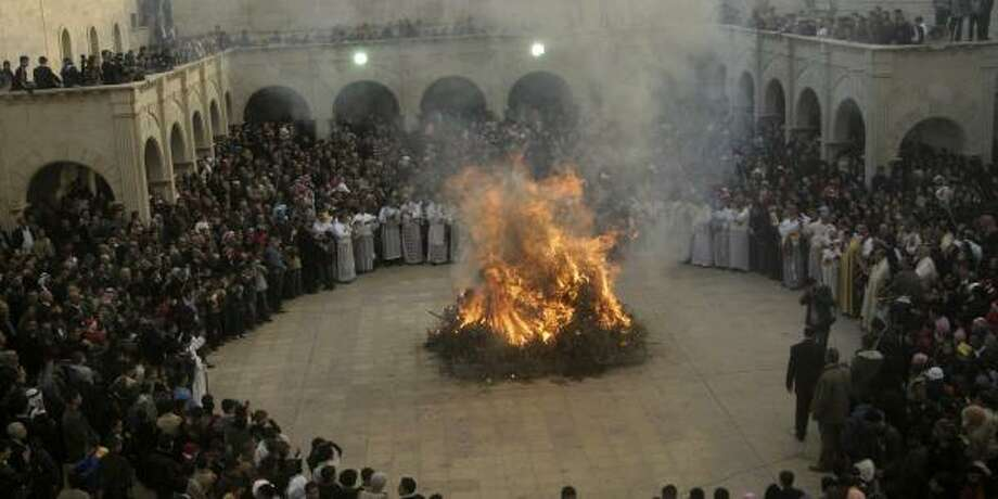 Iraqi Christians gather around a fire during Christmas Eve Mass at The Great Virgin Mariam Church in the Hamdaniya area, 19 miles east of Mosul. Fewer than 3 percent of Iraq's 26 million people are Christians. Photo: ASSOCIATED PRESS