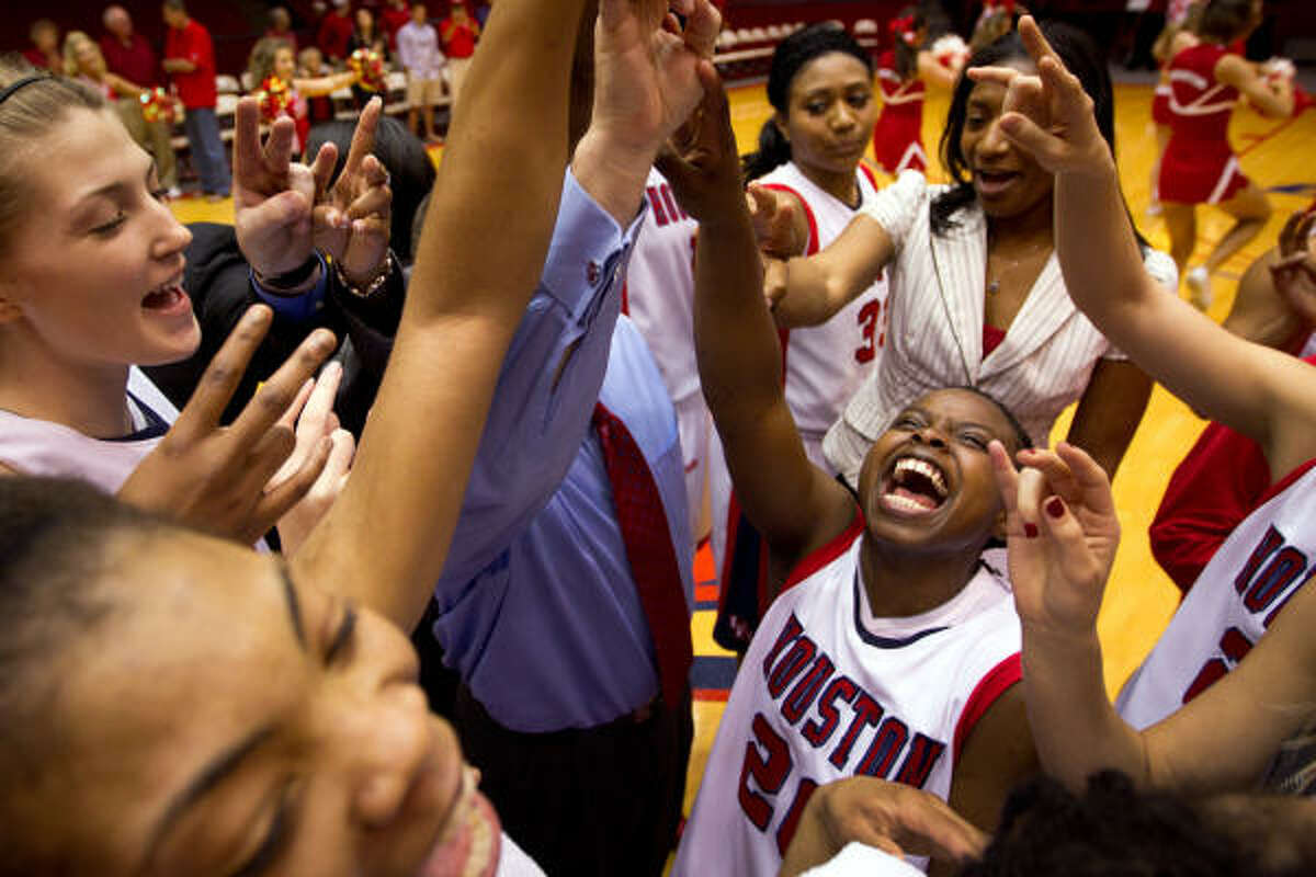 Cougars guard Porsche Landry (20) celebrates with her teammates following the Cougars victory.