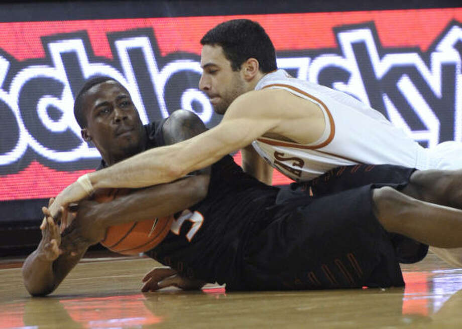 Feb. 16: No. 2 Texas 73, Oklahoma State 55 Oklahoma State guard Reger Dowell, left, recovers a loose ball from Texas guard Dogus Balbay during the second half of Wednesday's game. Photo: Michael Thomas, AP