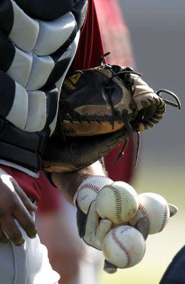 Catcher Carlos Corporan dumps balls into a basket. Photo: Karen Warren, Chronicle