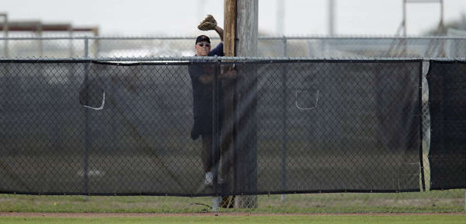 An unidentified Astros fan perches himself just behind the fence in one of the back fields as he waits for home run balls being hit by the catchers. Photo: Karen Warren, Chronicle