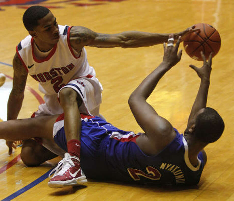 Feb. 16: SMU 65, UH 51UH guard Zamal Nixon, left, and SMU's Robert Nyakundi scramble for a loose ball during the second half of Wednesday night's game at Hofheinz Pavilion. The Cougars were left scrambling after suffering their sixth loss in seven games and falling to 12-12. Photo: Melissa Phillip, Chronicle
