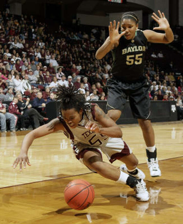 Texas A&M's Danielle Gant, left, loses the ball as she falls while Baylor's Morghan Medlock, right, defends during the first half of an Wednesday. Photo: David J. Phillip, AP