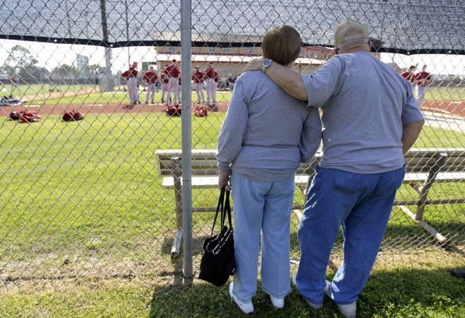 A couple of fans watch as the pitchers chat before their first throwing session. Photo: Karen Warren, Chronicle