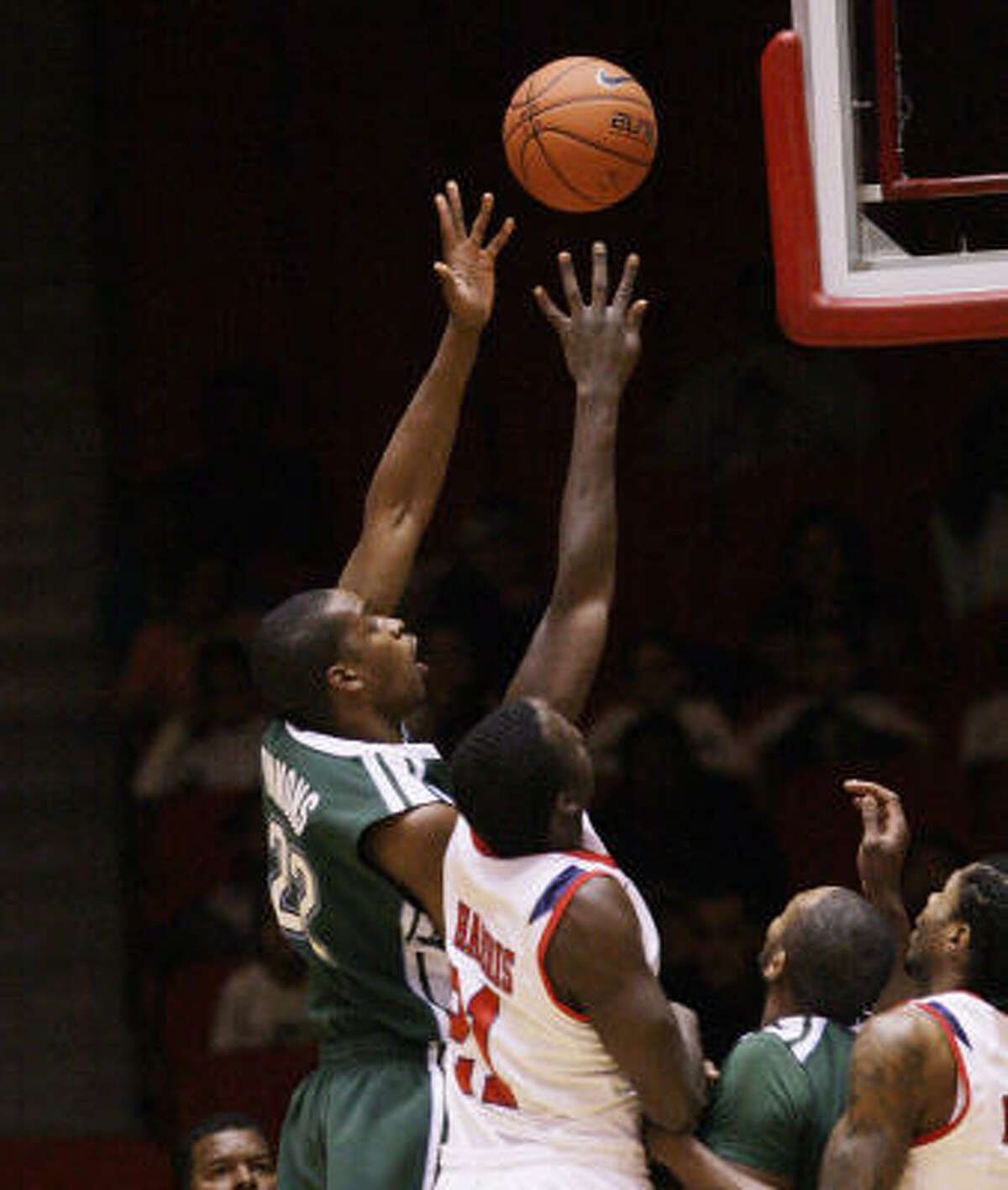 Tulane's Kendall Timmons (22) drives to the basket over UH forward Alandise Harris.