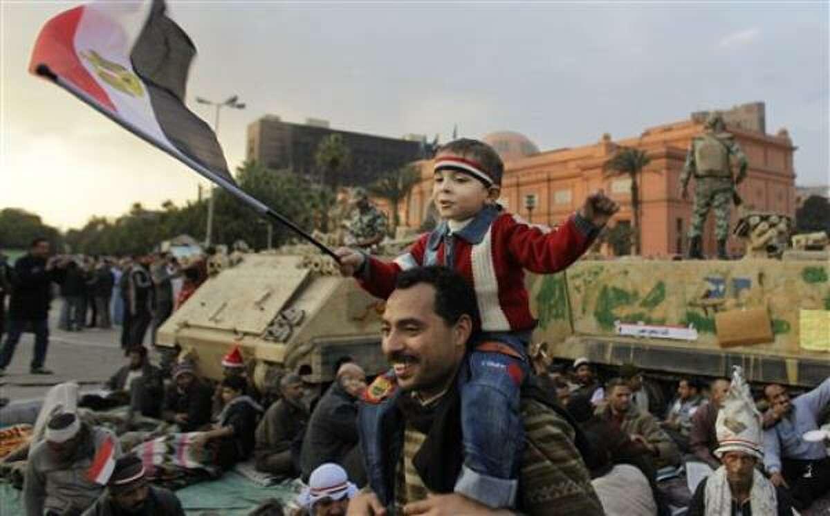 Un joven manifestante antigubernamental sentado en los hombros de un familiar flamea la bandera egipcia frente un vehículo blindado de transporte de personal en medio de las protestas que continúan en la plaza Tahrir Square en el centro de El Cairo, Egipto el lunes 7 de febrero del 2011.