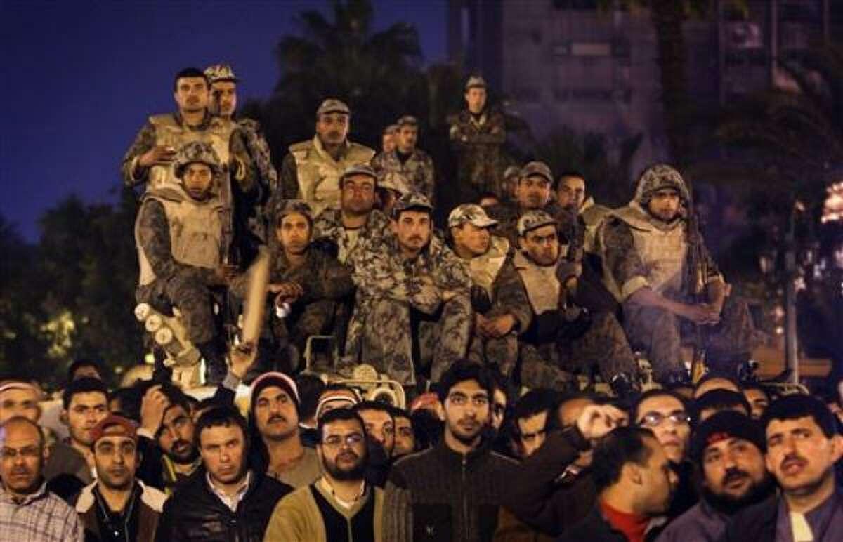 Manifestantes antigubernamentales y soldados egipcios observan en una pantalla de la plaza Tahrir de El Cairo al presidente egipcio Hosni Mubarak mientras pronuncia un discurso por televisión el jueves 10 de febrero del 2011.