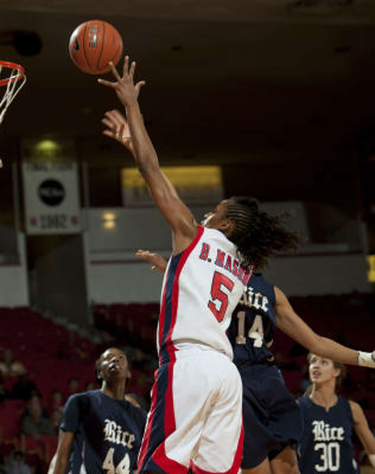 UH's Brittany Mason (5) drives to the basket over Rice's Brianna Hypolite (14) during the second half.