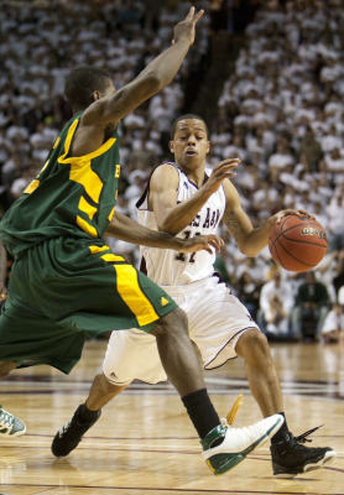 Texas A&M's B.J. Holmes, right, drives the ball against Baylor defender A.J. Walton, left.