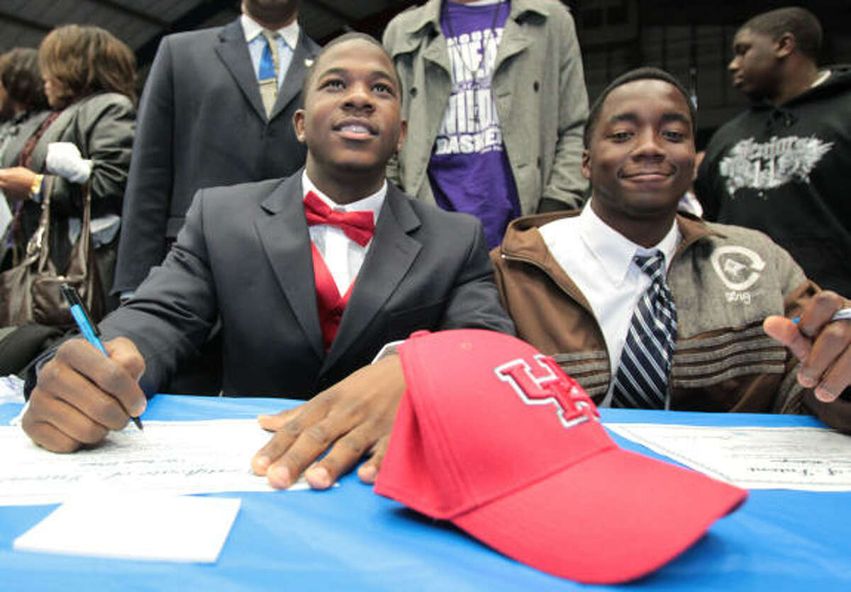 Wheatley's Devonte Potier signs his letter of intent to play football at UH while teammate Jovon Washington signs with Lon Morris College.