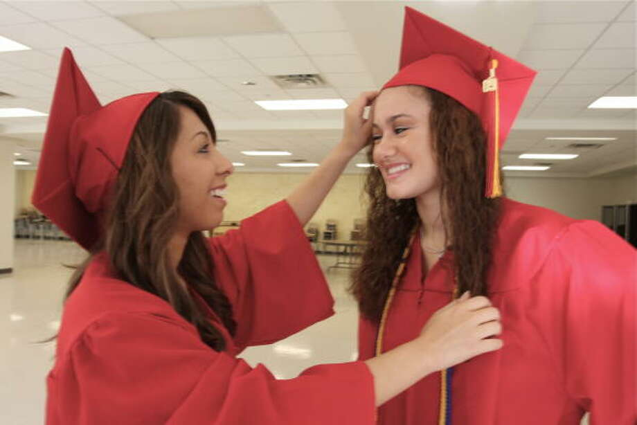 Kristina Reyna, 18, of Sugar Land helps Jessica Tello, 18, of Katy with her hat before May 23 commencement at  Pope John XXIII High School in Katy. Photo: Suzanne Rehak, For The Chronicle