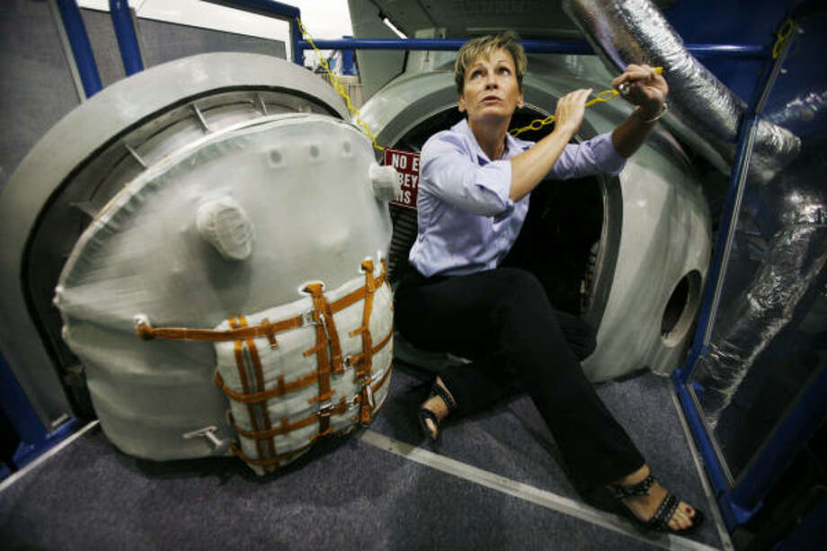 Biochemist Peggy Whitson, showing off a Soyuz capsule mock-up, lauds the scientific capacity of the space station, where she has spent more than a year total in two separate tours. Photo: Eric Kayne, Chronicle