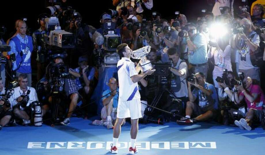Jan. 30Novak Djokovic kisses his trophy in front of a row of photographers after defeating Andy Murray in the men's singles final. Photo: Vincent Thian, AP