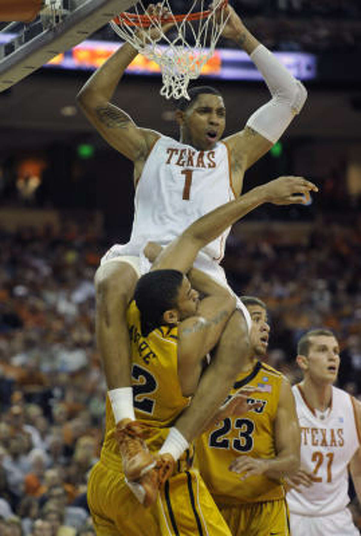 Texas forward Gary Johnson, top, holds onto the rim while wrapped around Missouri center Steve Moore after attempting a dunk during the first half.