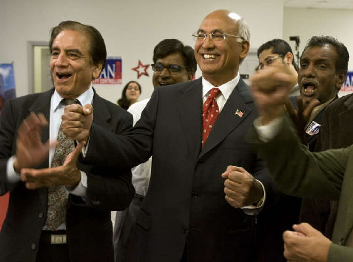 Aqeel Ashraf, left, and candidate M.J. Khan, center, react as the vote totals come in Tuesday night.