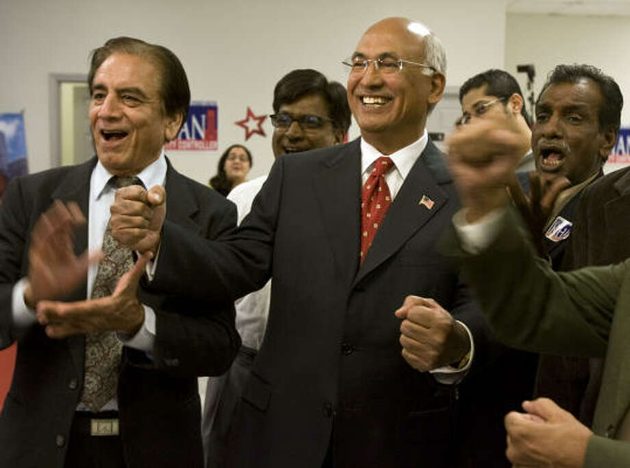 Aqeel Ashraf, left, and candidate M.J. Khan, center, react as the vote totals come in Tuesday night. Photo: James Nielsen, Chronicle