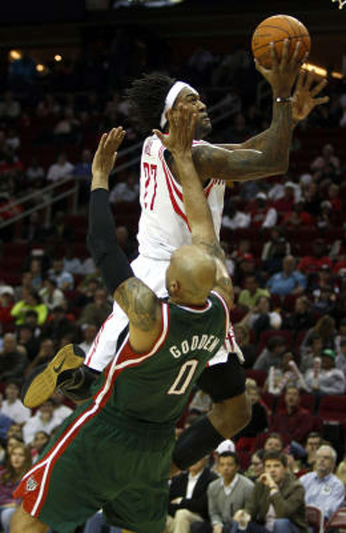 Rockets center Jordan Hill charges into Bucks center Drew Gooden.