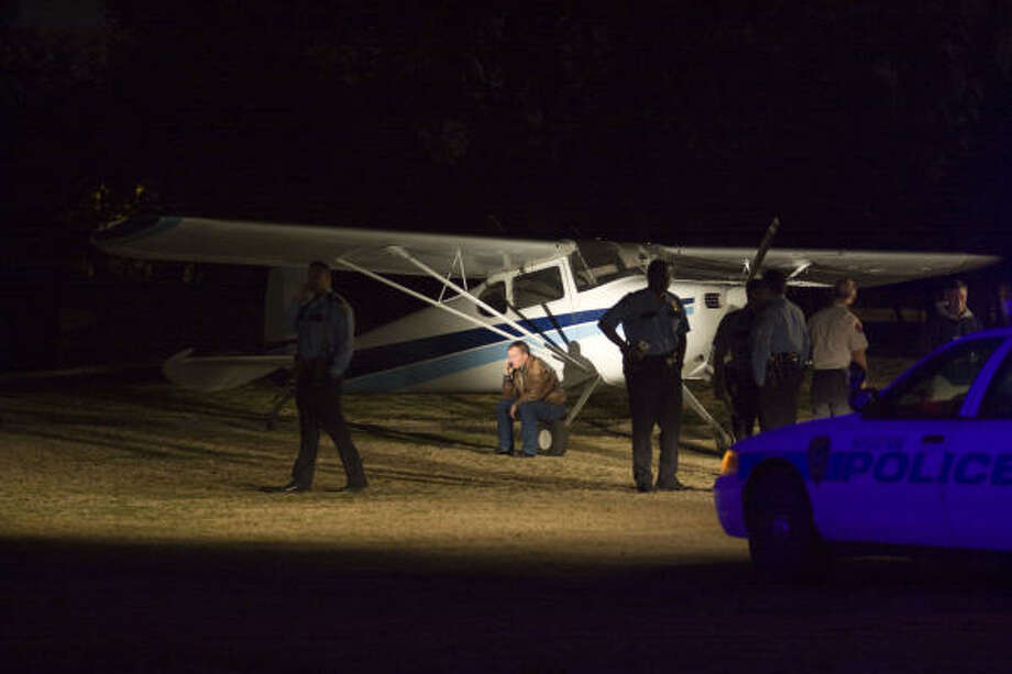 Pilot Brendon Ford talks on a cell phone Monday after landing a single-engine Cessna on the 11th hole fairway at Hermann Park Golf Course. Photo: Eric Kayne, For The Chronicle