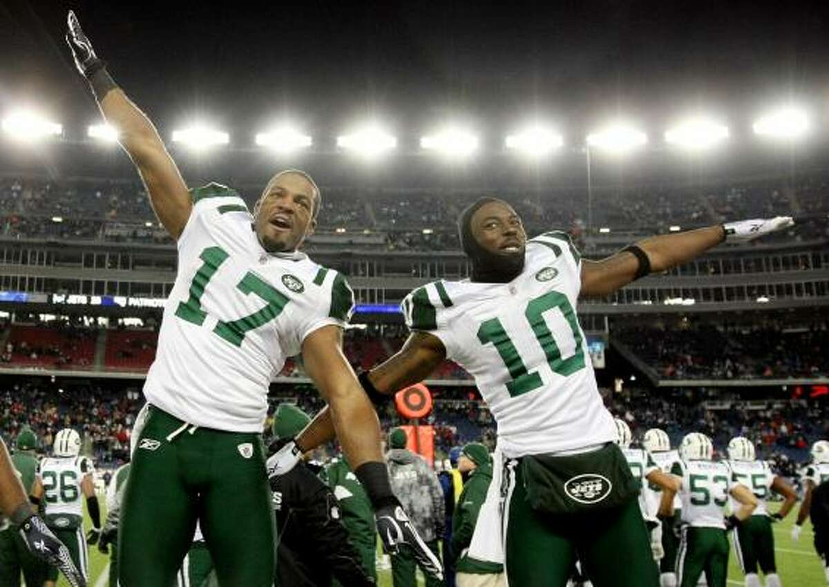 Jets receivers Braylon Edwards, left, and Santonio Holmes celebrate their victory over the New England Patriots.
