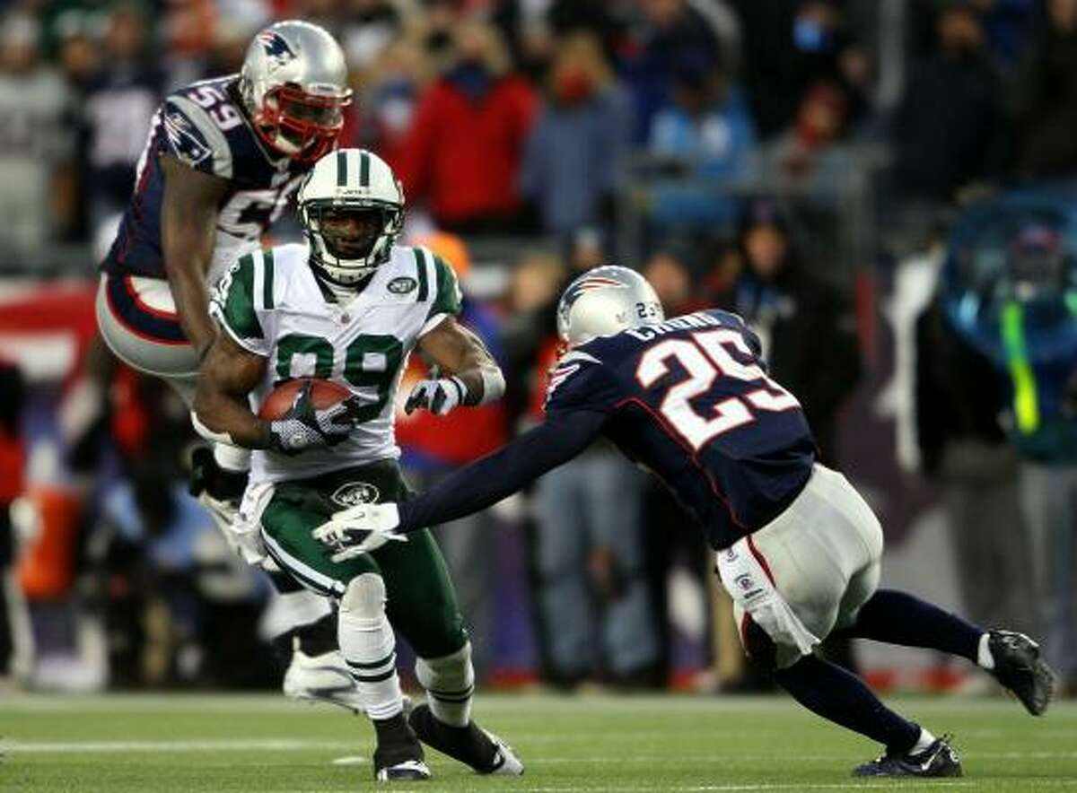 Jets wide receiver Jerricho Cotchery tries to avoid the tackle of Patriots safety Pat Chung (25) and linebacker Gary Guyton (59).